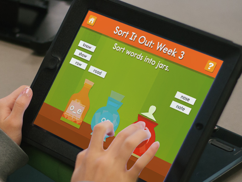 word game app screen shown in iPad being held by user